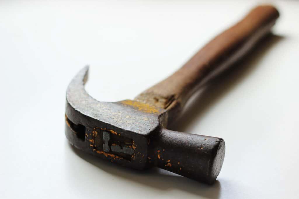 foto de um martelo unha com cabo de madeira e fundo branco.