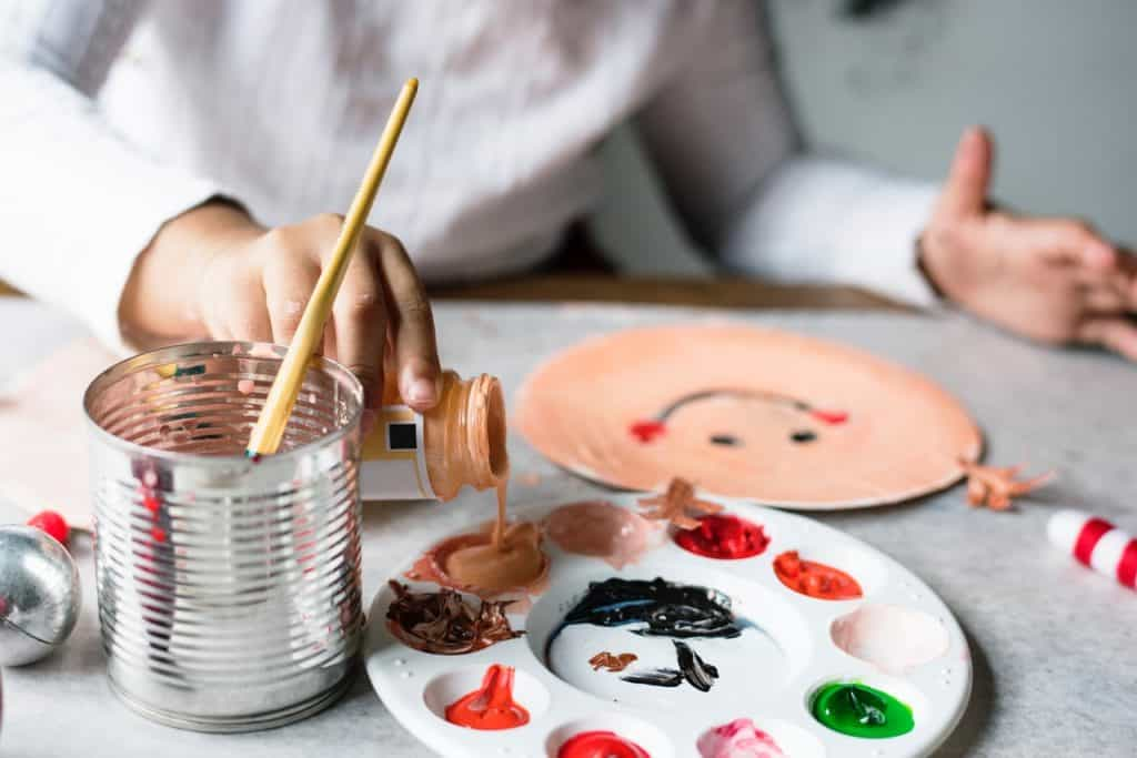 Pessoa usa superfície própria para dispor diversas cores de tinta óleo.
