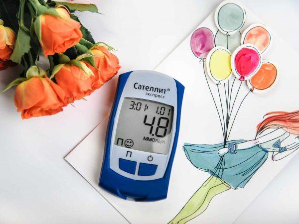 Um medidor de glicemia em cima de um papel de carta e ao lado de algumas flores.