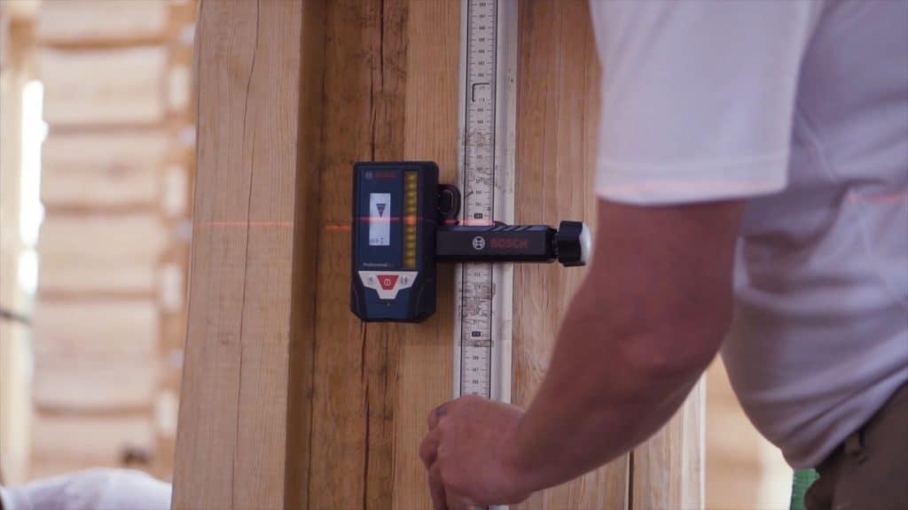 Homem fazendo medição usando uma trena a laser.
