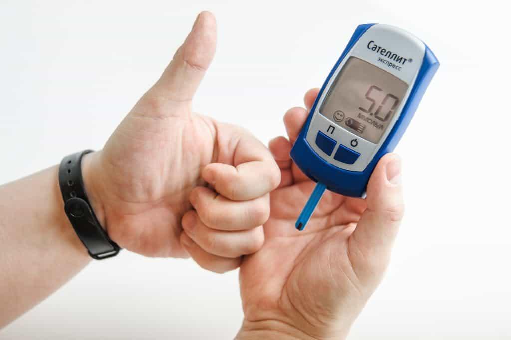 Uma pessoa segurando o medidor de glicemia com a mão direita e fazendo um sinal de positivo com a mão esquerda.