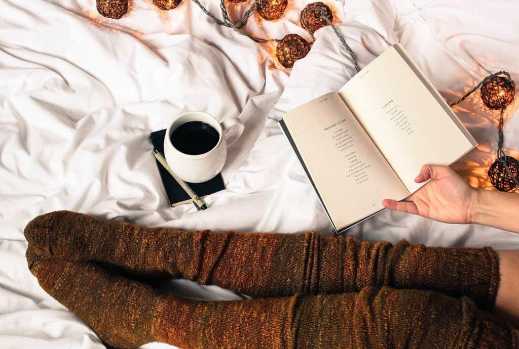 Pernas com meia de cano alto de lã sobre a cama ao lado de livro e xícara de café.