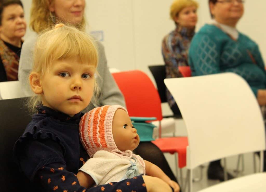 Menina com boneca bebê no colo.
