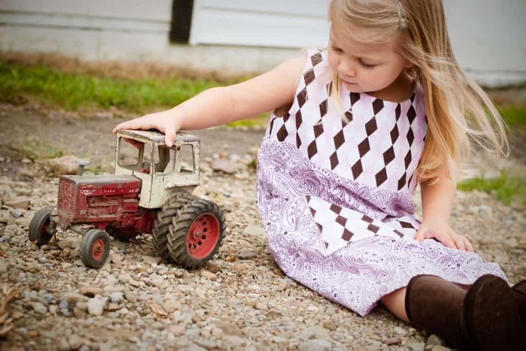 Imagem mostra uma menina empurrando um trator de brinquedo.