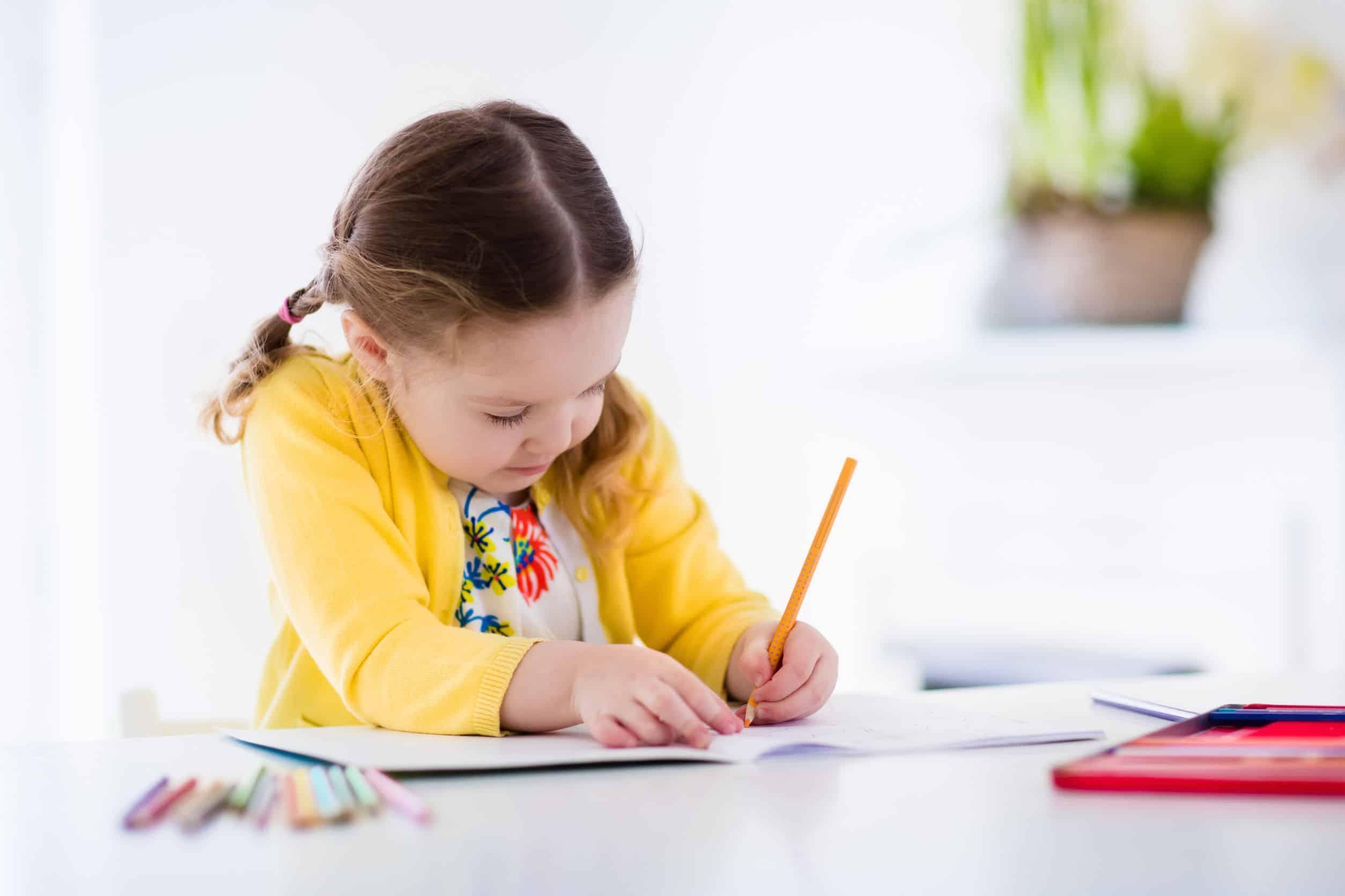 Foto de uma menina pintando um livro de colorir.
