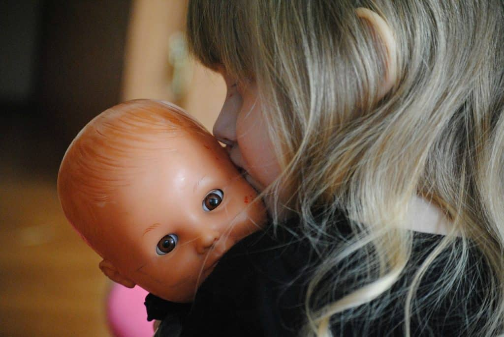 Menina segurando boneca bebê.