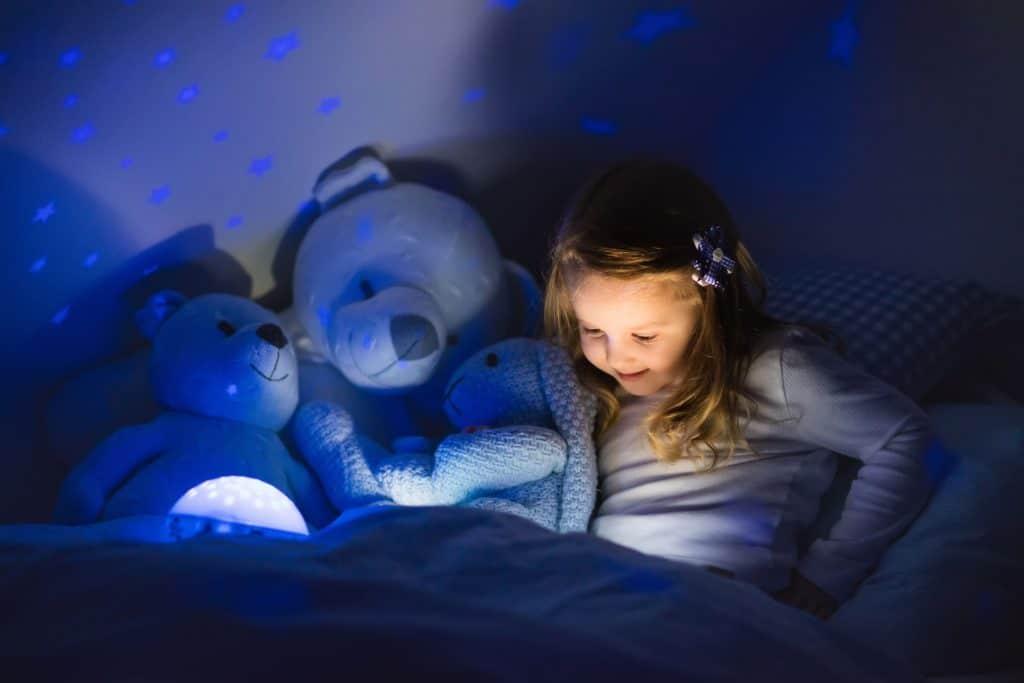Menina lendo em quarto parcialmente escuro com luz focada no livro.