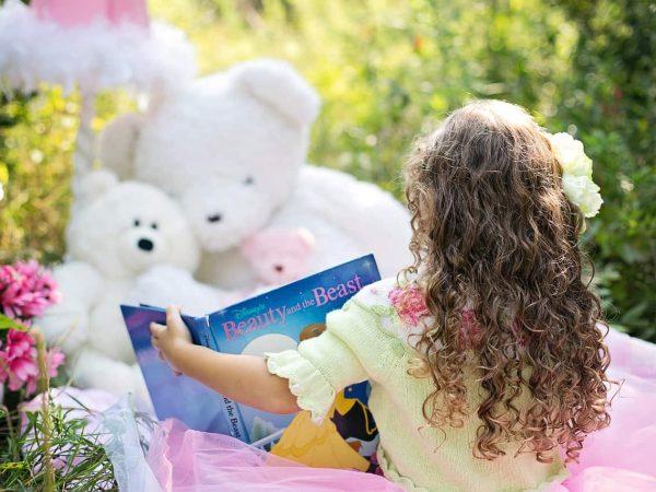 Na foto uma menina de cabelos enrolados sentada em um jardim com um livro da Bela e a Fera em frente a dois ursinhos de pelúcia.