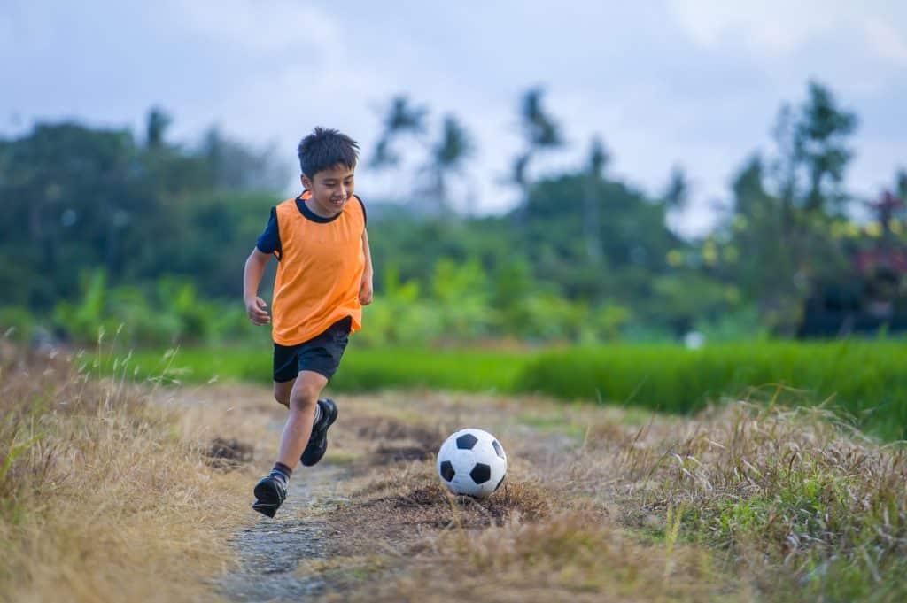 menino jogando futebol com colete esportivo