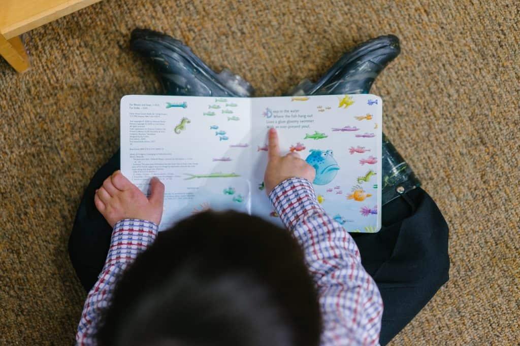 Na foto um menino sentado no chão com camiseta xadrez e bota lendo um livro ilustrado.