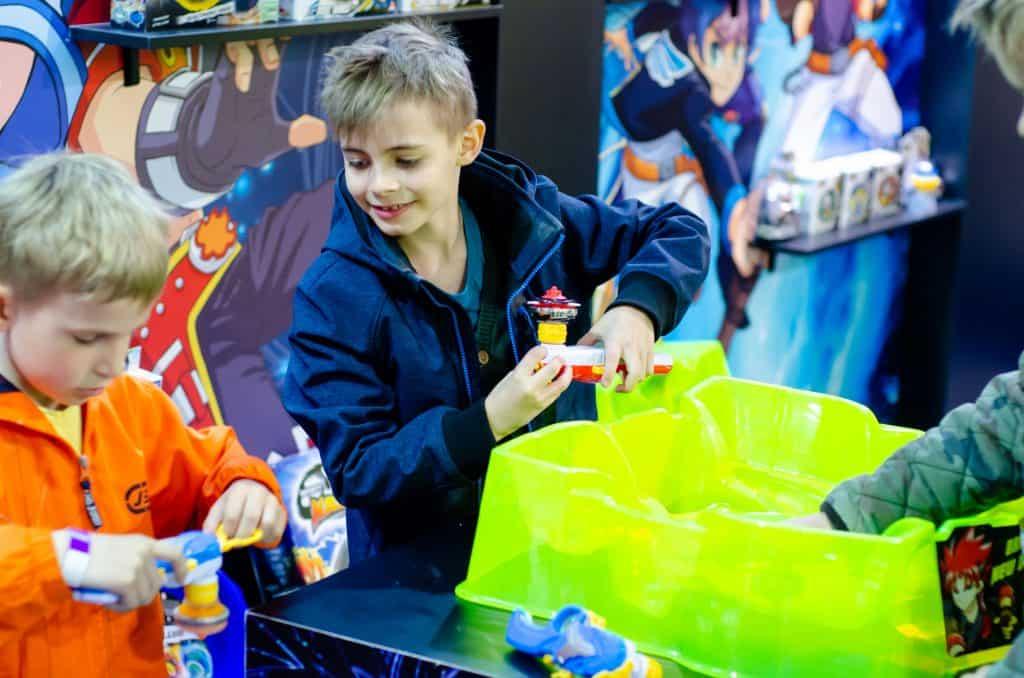 Em uma sala com decoração do desenho Beyblade há 3 crianças brincando com o brinquedo Beyblade em uma arena da geração 3