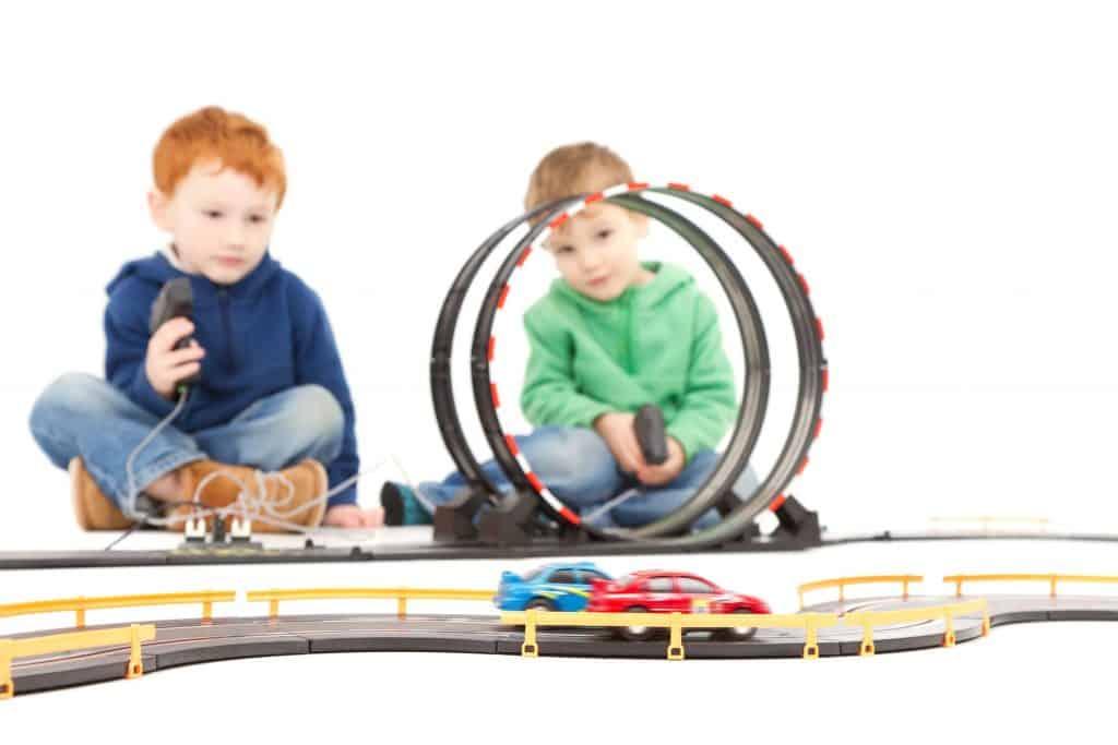 Dois garotos brincando com uma pista de corrida, com loopings e carrinhos de controle.