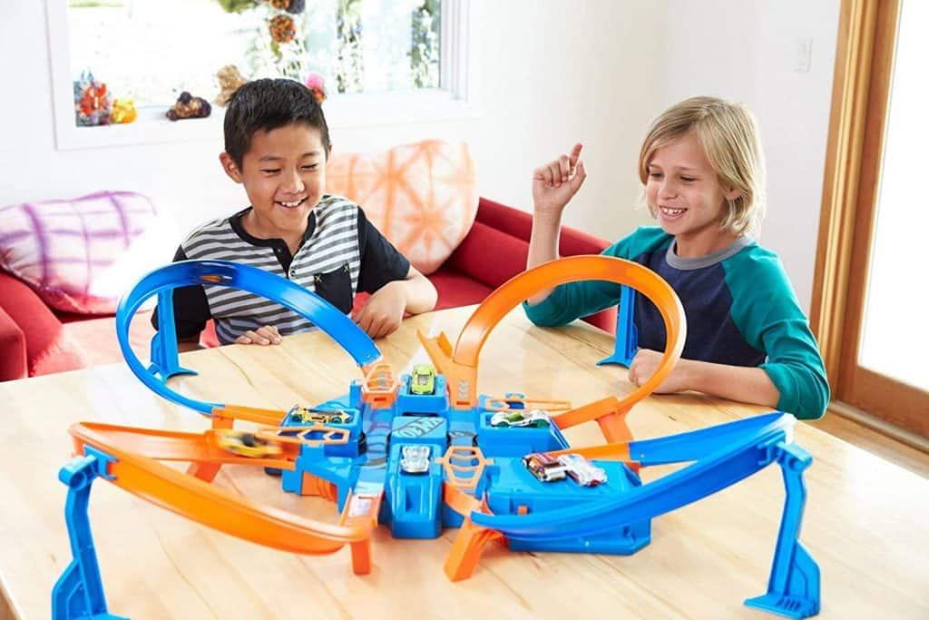 Dois meninos brincando com uma pista hot wheels.