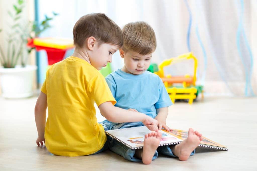Na foto dois meninos sentados no chão olhando para um livro.