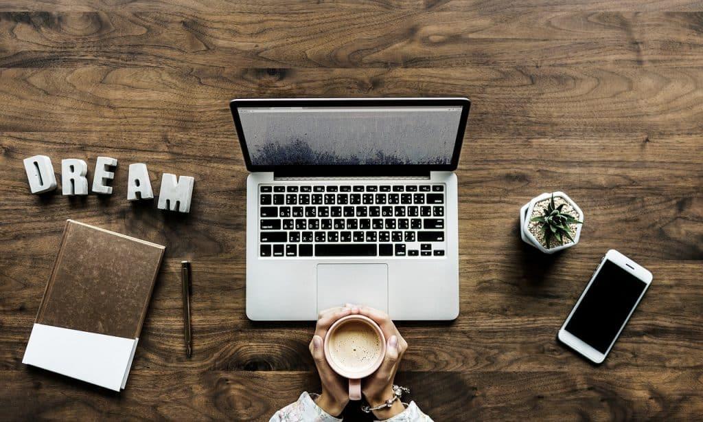 Imagem mostra um notebook em cima de uma mesa de madeira em frente a uma pessoa com uma caneca de café na mão.
