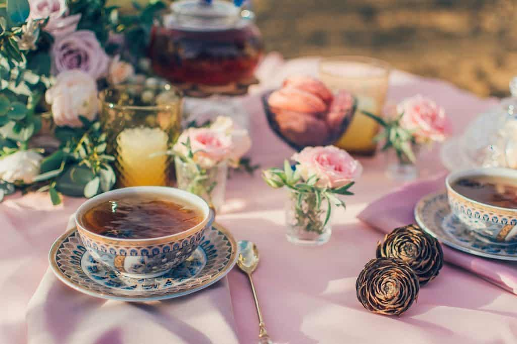 Imagem de serviço de chá com xícaras estampadas com motivos geométricos e florais sobre mesa decorada com flores.