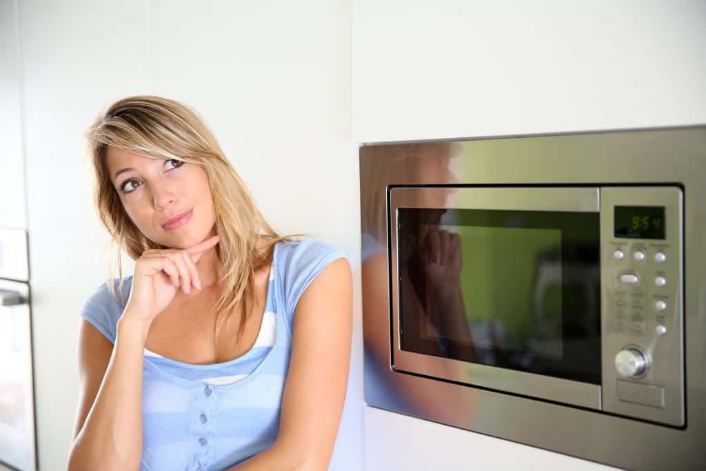 Foto de uma mulher loira de blusa azul, com expressão pensativa ao lado de um micro-ondas embutido.