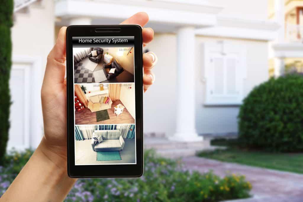 Mão de mulher segurando um smartphone em frente a sua casa e vendo as câmeras de vigilância.