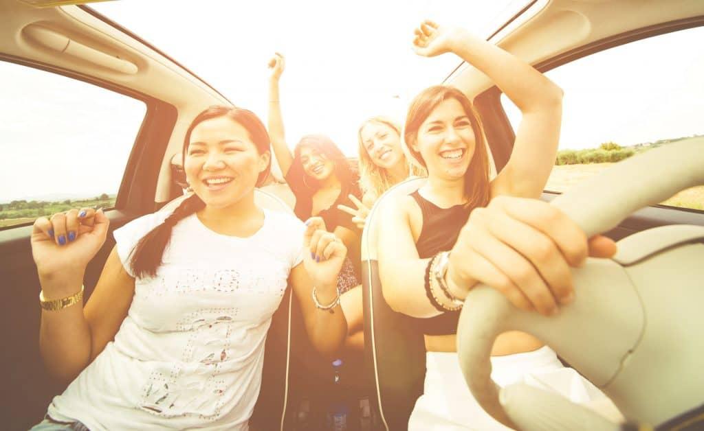 Amigas escutando música e dançando em carro com teto solar aberto.