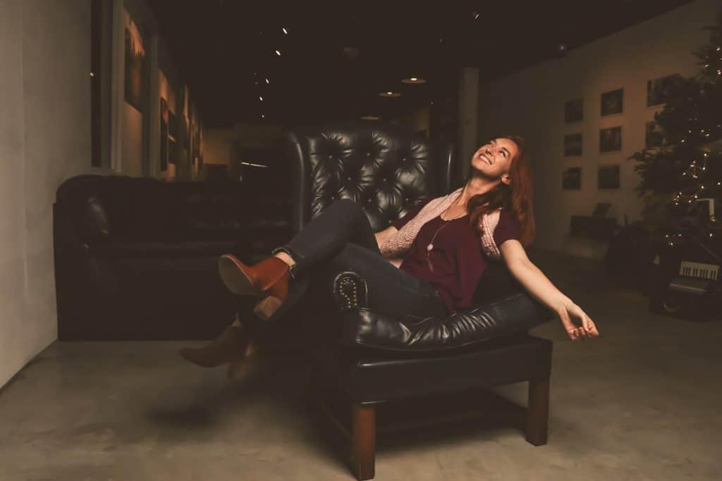 Foto de uma mulher sentada de lado em uma cadeira de couro, olhando pra cima. Ela veste calça jeans, camiseta, botas e cachecol. Ao fundo, uma árvore de natal, sofá e quadros.