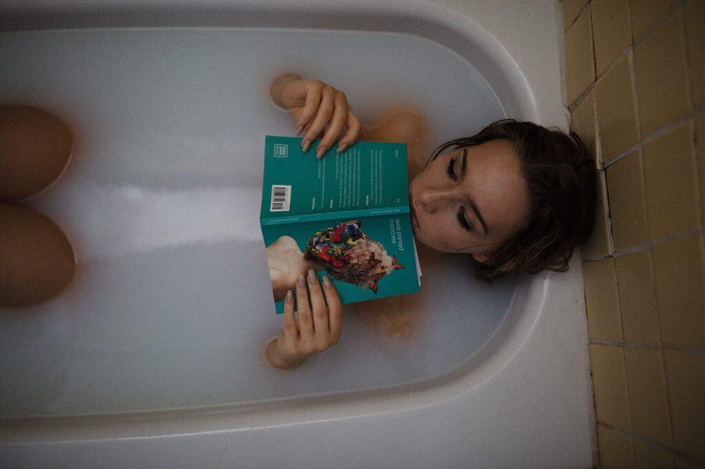 Mulher deitada em uma banheira cheia, relaxando com um livro em mãos.