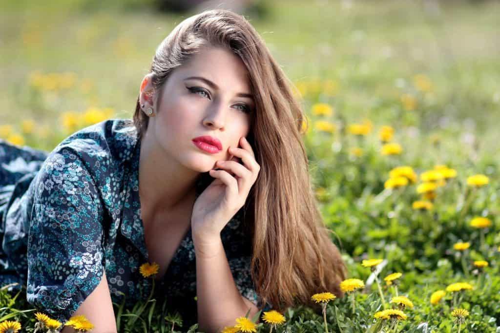 Imagem de uma mulher deitada em um campo de flores.