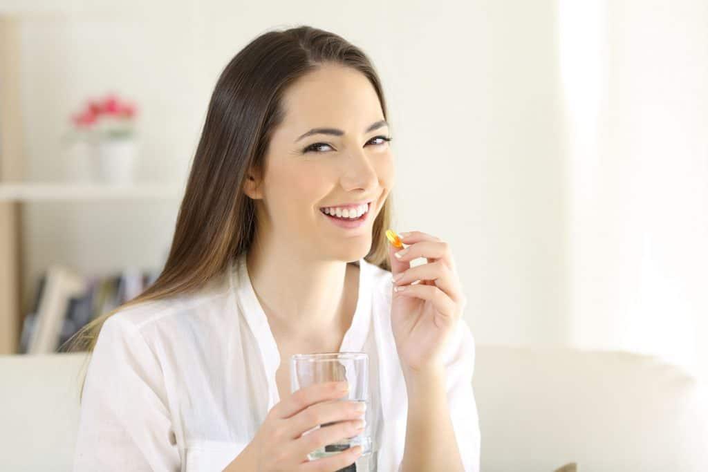 Mulher tomando comprimido com copo de água.