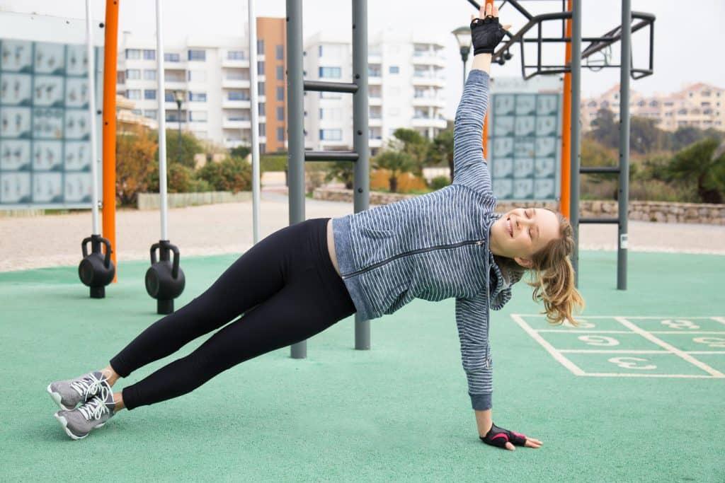 Moça utiliza luvas esportivas ao se exercitar em academia ao ar livre.