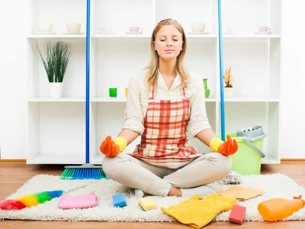 Mulher sentada, meditando, no meio de vassouras, balde, e acessórios de faxina.