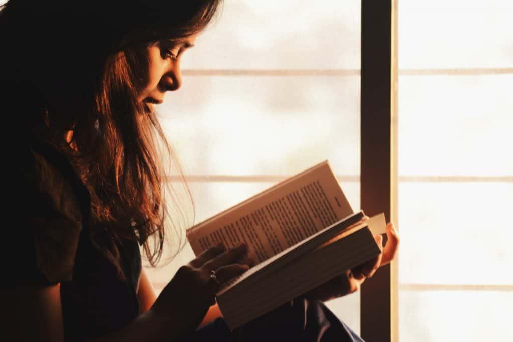 Foto de uma mulher sentada de lado, lendo um livro grosso, dentro de um espaço fechado com pouca claridade, próxima a uma janela.