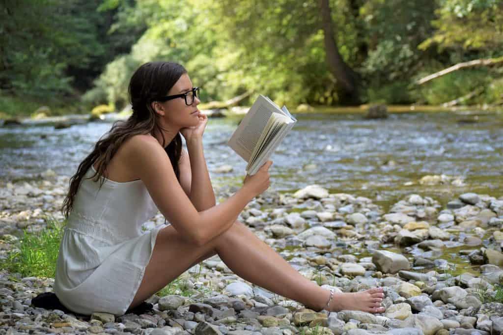 Mulher sentada na beira de um rio lendo livro.