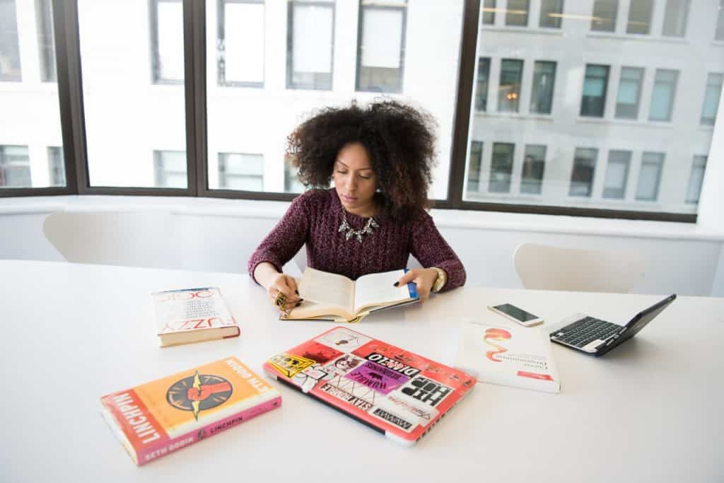 Imagem de uma mulher lendo livros de administração.
