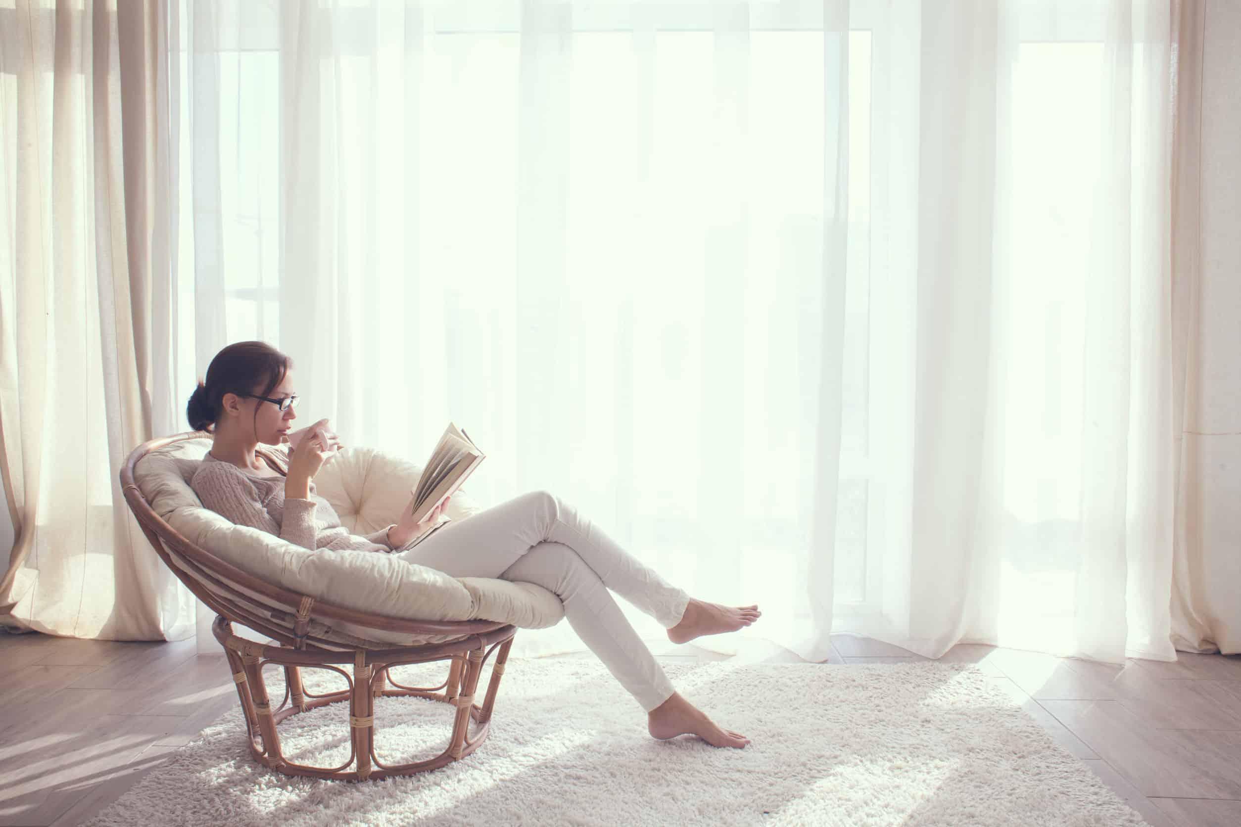 Na foto uma mulher sentada em uma poltrona com uma xícara na mão e um livro.