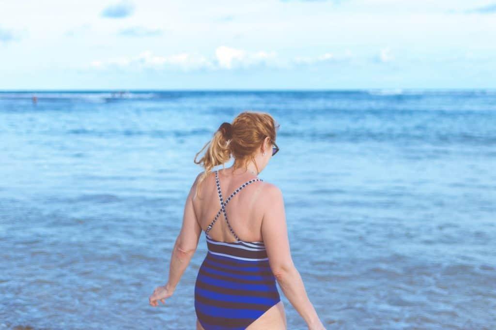Imagem de uma menina usando maiô na praia.