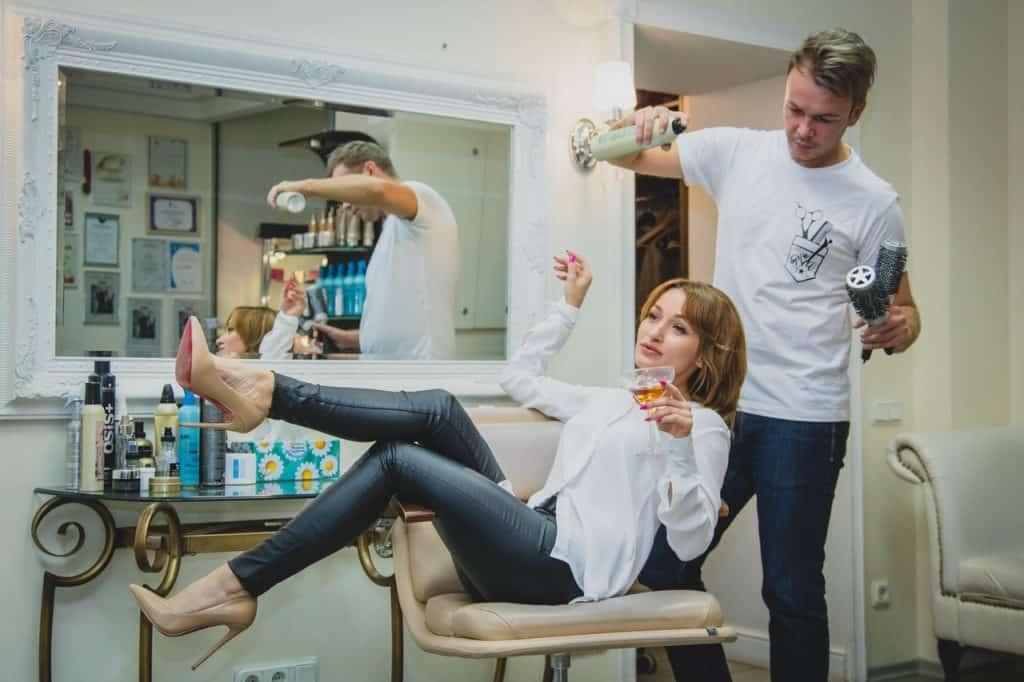 Foto de uma mulher em salão de beleza, sentada em uma cadeira com as pernas para o alto, segurando uma taça de bebida. Ao seu lado, um cabeleireiro espirra um spray no seu cabelo e segura duas escovas de cabelo.