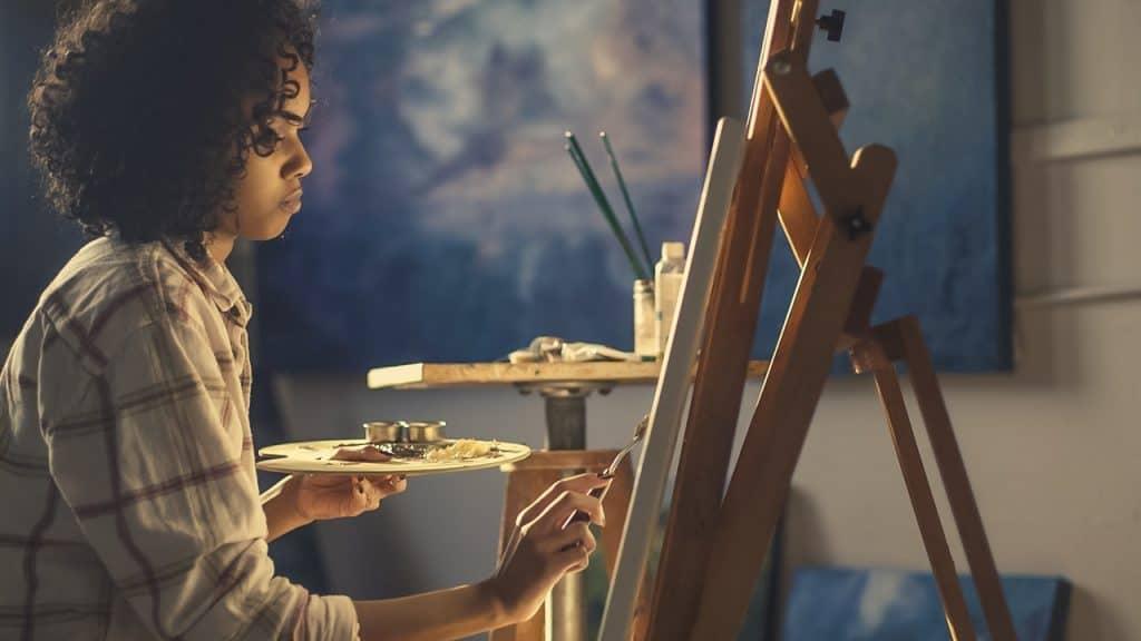 Moça pinta com tinta óleo sobre tela usando espátula.