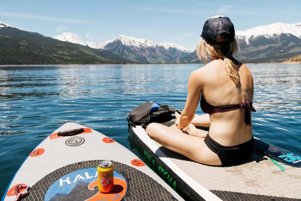 Imagem mostra uma moça sentada num stand up inflável. Ao seu lado há outra prancha, com uma lata de bebida descansando sobre seu deck.