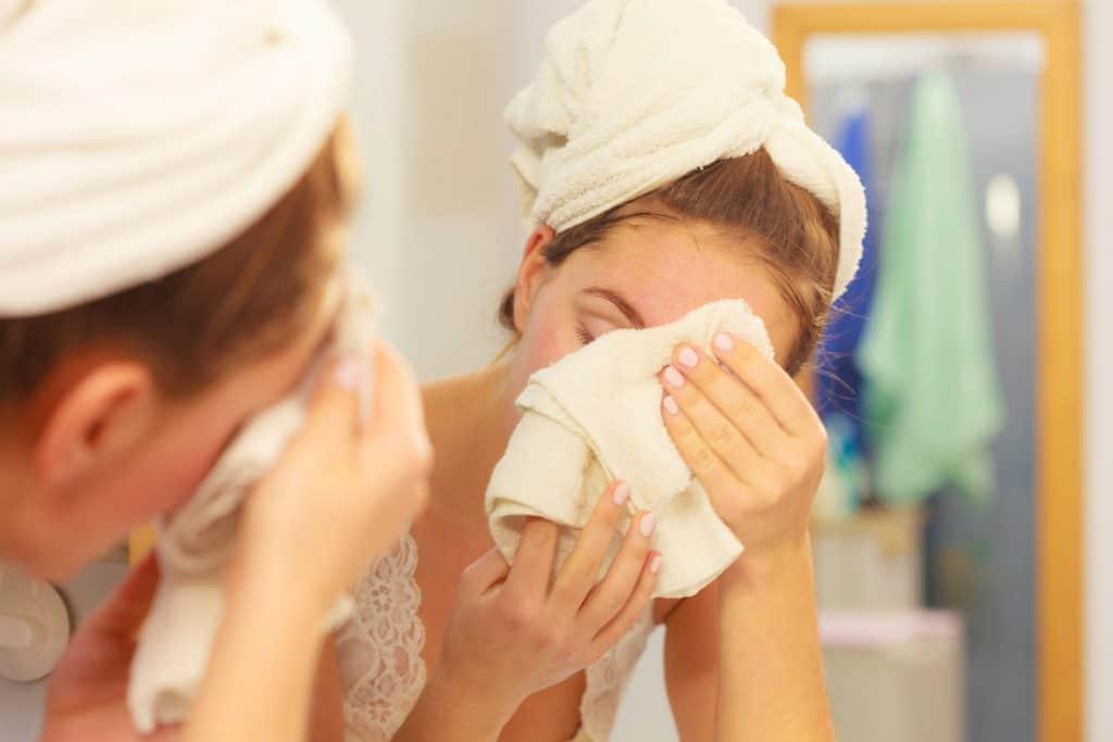 Na foto uma mulher com toalha nos cabelos secando o rosto com uma toalha em frente a um espelho.