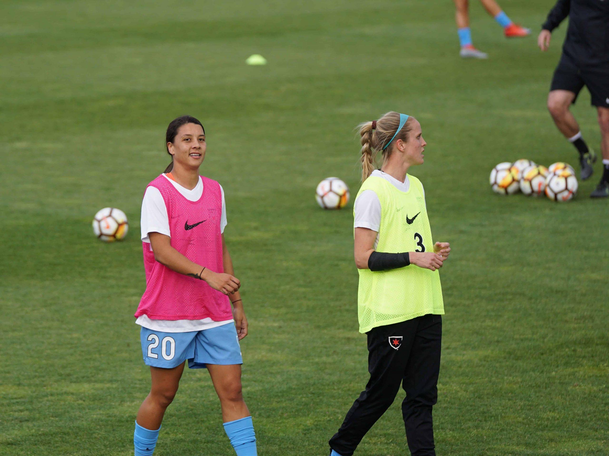 Imagem mostra duas jogadoras de futebol lado a lado, durante um treinamento. A da esquerda usa um colete rosa, o da direita, amarelo.