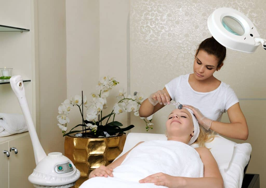 Na foto uma mulher deitada dentro de uma sala de esteticista com uma outra mulher cuidando do rosto dela.