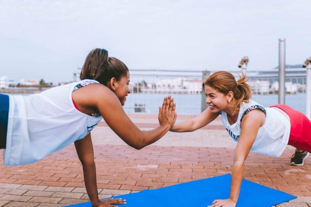 Duas moças se exercitam juntas ao ar livre