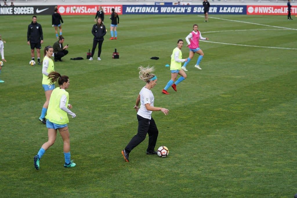 Imagem mostra cinco jogadoras de futebol durante uma atividade de treinamento. Três usam um colete claro, uma usa um colete escuro e a jogadora com a bola nos pés, apenas uma camiseta.