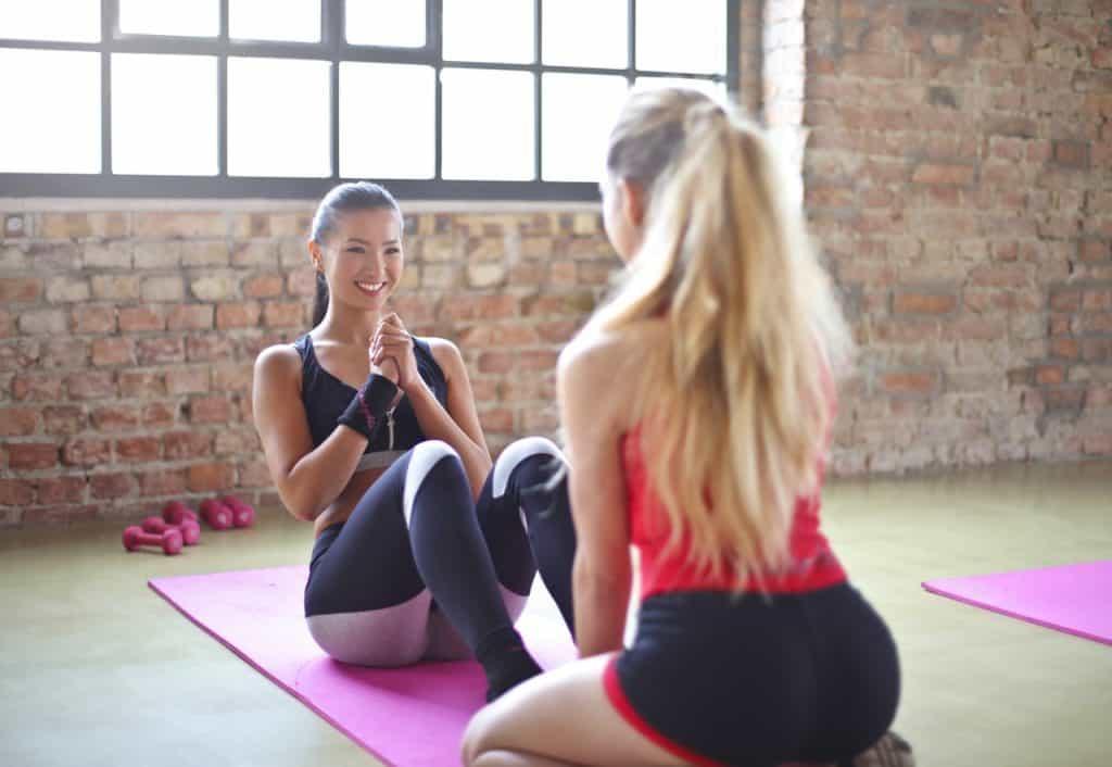 Moças fazem abdominais em dupla sobre colchonetes de academia