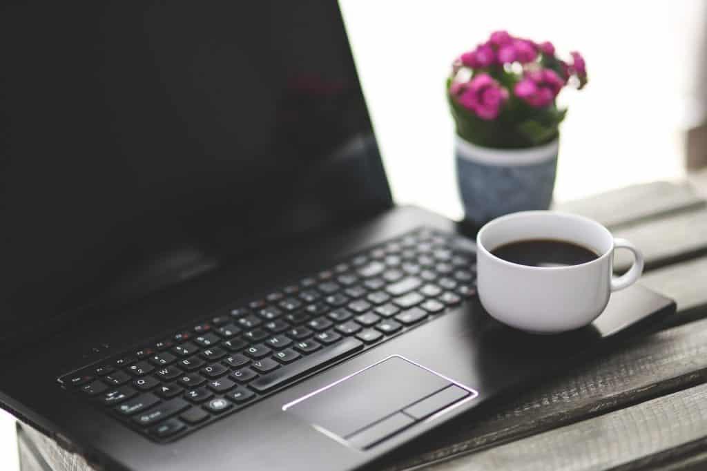 Notebook sobre mesa de madeira ao lado de vaso de flores e com xícara de café apoiada.