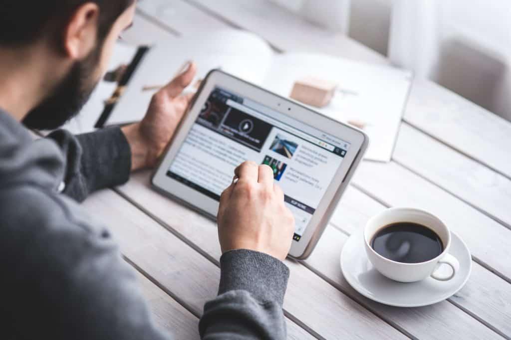 Na foto um homem sentado usando um notebook dobrável sobre uma mesa de madeira com uma xícara de café ao lado.