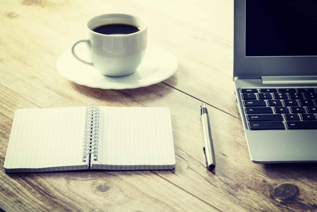 Imagem mostra um notebook prata ao lado de um caderno, caneta e xícara de café.