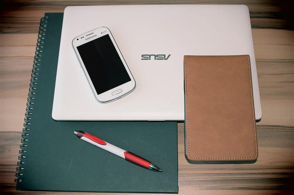 Na foto um notebook em cima de um caderno sobre uma mesa de madeira com um celular, um bloco de anotações e uma caneta.