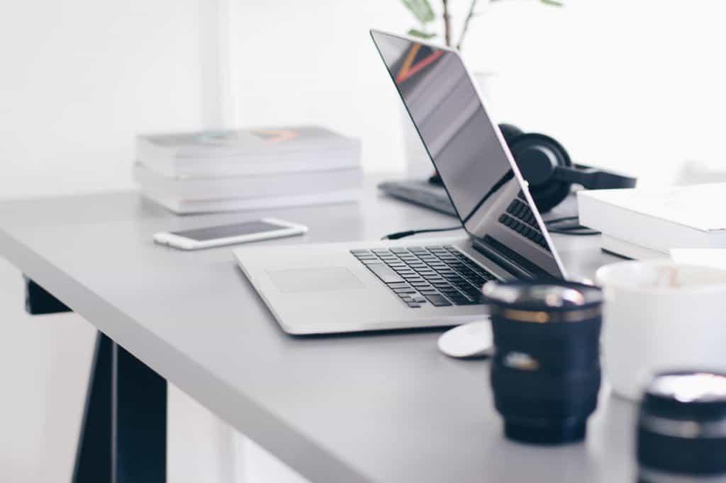 Na foto um notebook em cima de uma mesa com duas lentes de câmera na direita e um celular na esquerda.