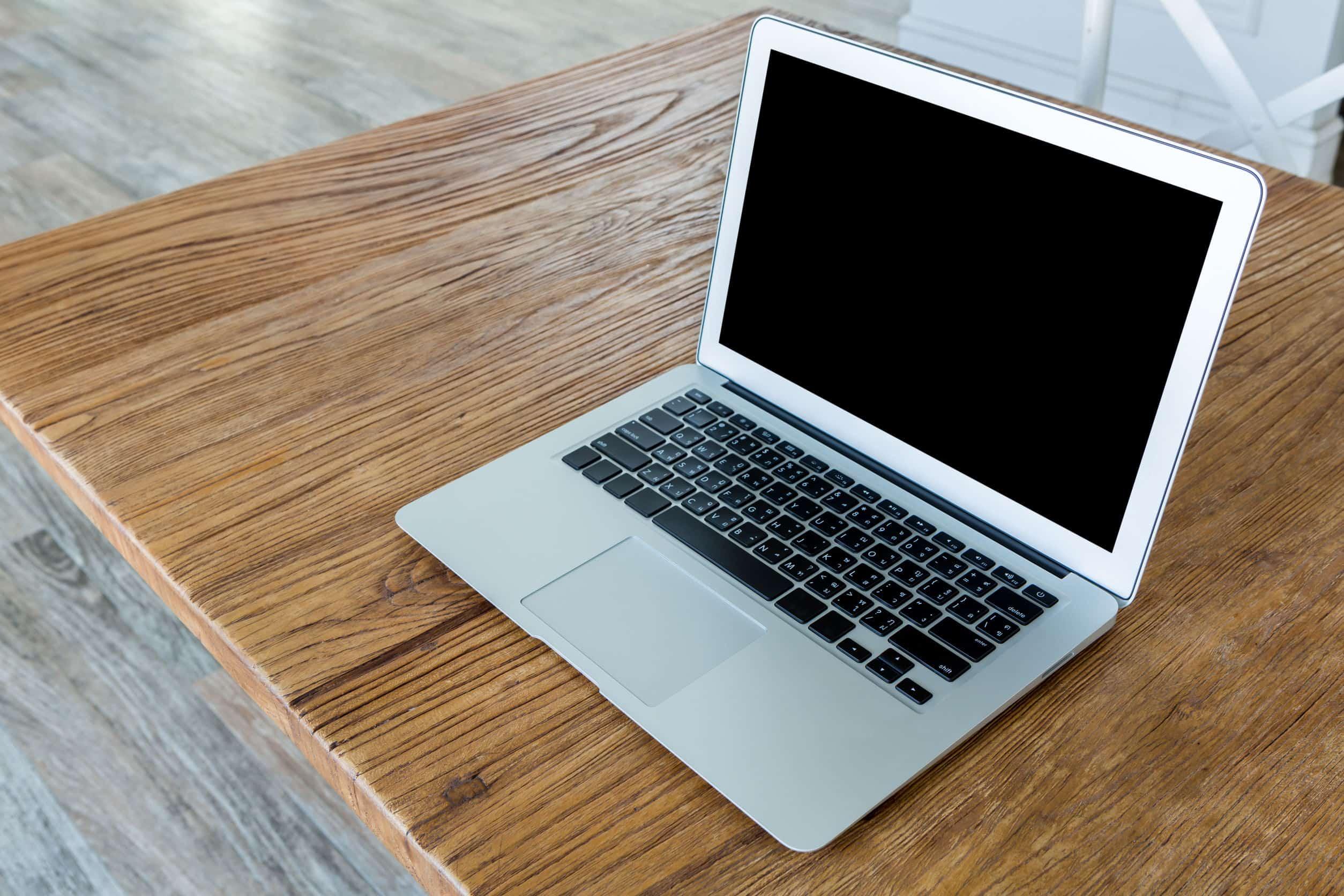 Imagem mostra um notebook aberto da Lenovo na cor cinza sobre mesa.