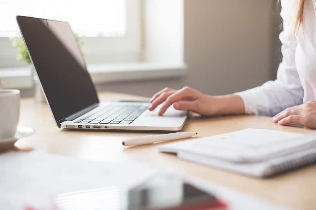 Moça usando um notebook em sua mesa de trabalho.